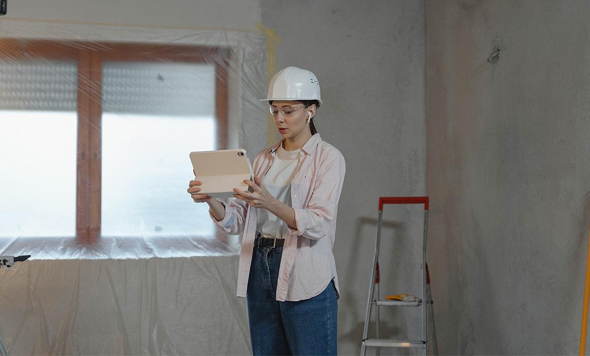 Femme photographiant un chantier avec une tablette