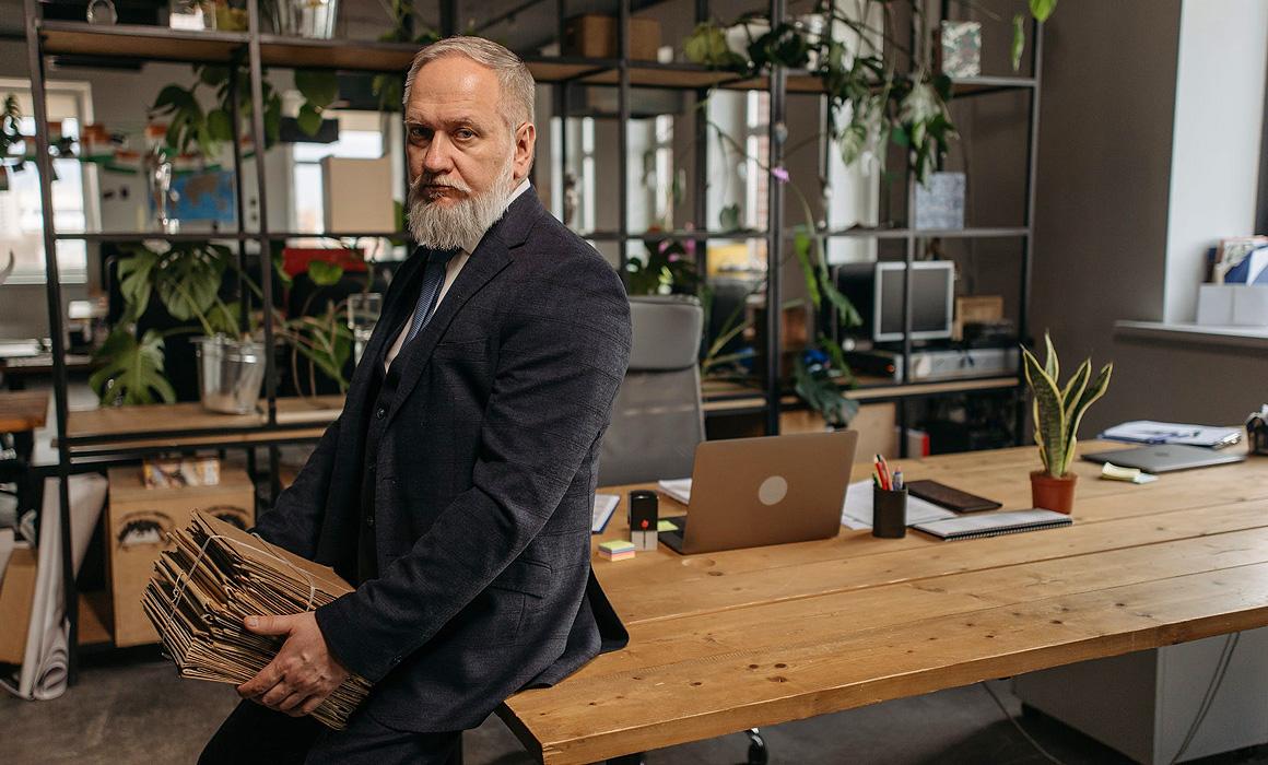 Homme assis sur une table portant des dossiers