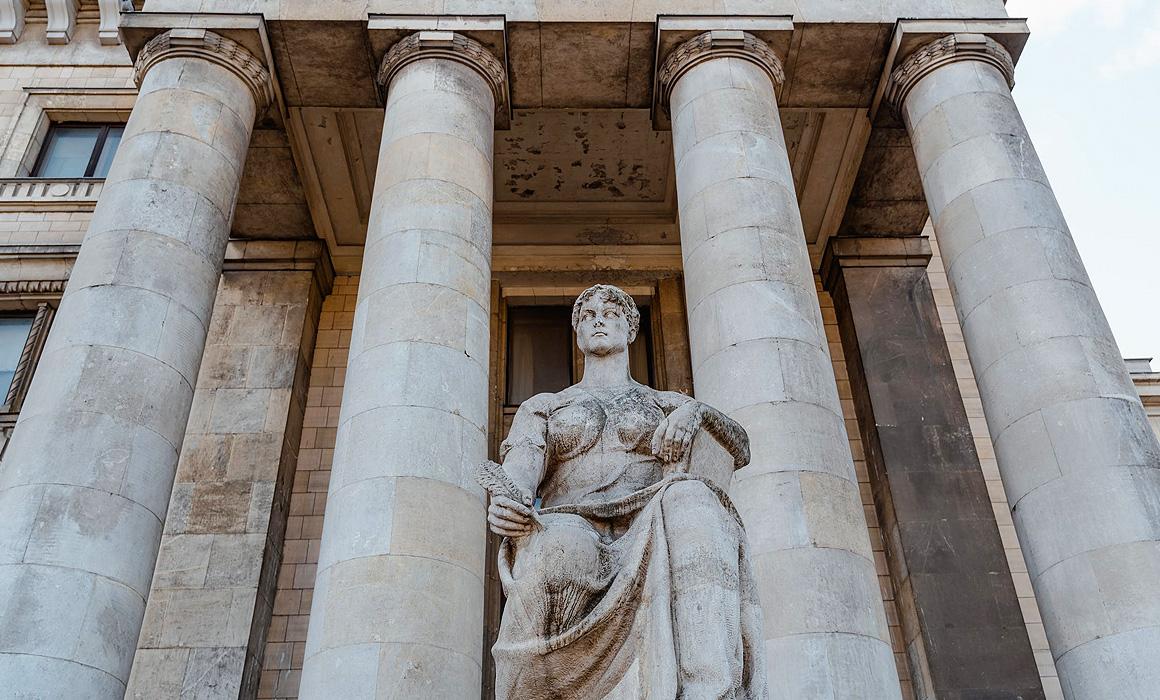 Statue devant bâtiment à colonnades