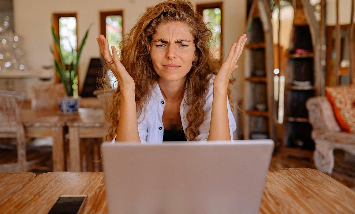 Femme agacée devant l'écran de son ordinateur portable