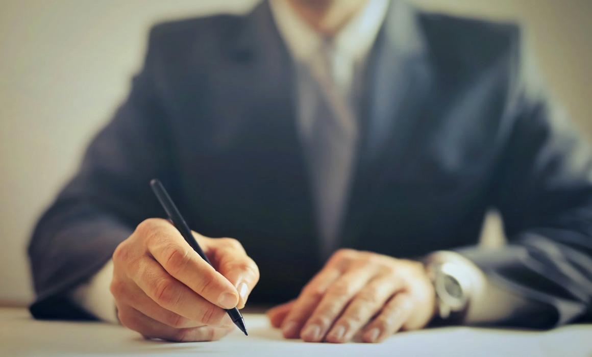 Homme écrivant sur une feuille de papier