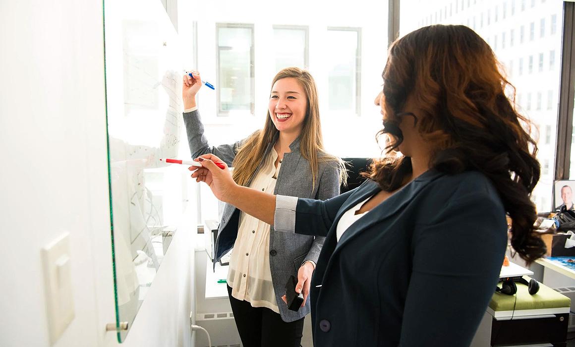 Femmes écrivant sur un tableau blanc