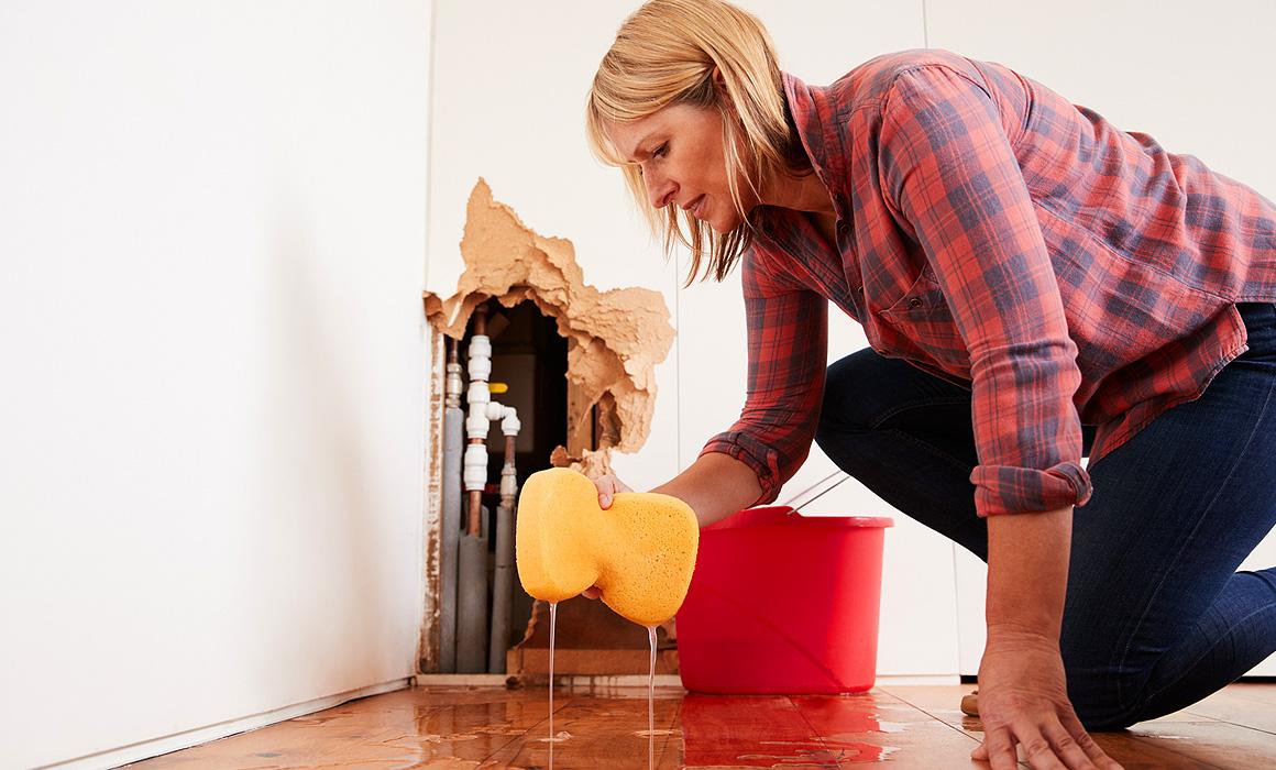 Femme épongeant un dégât des eaux