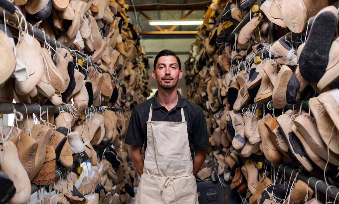Artisan posant devant des rayons de chaussures