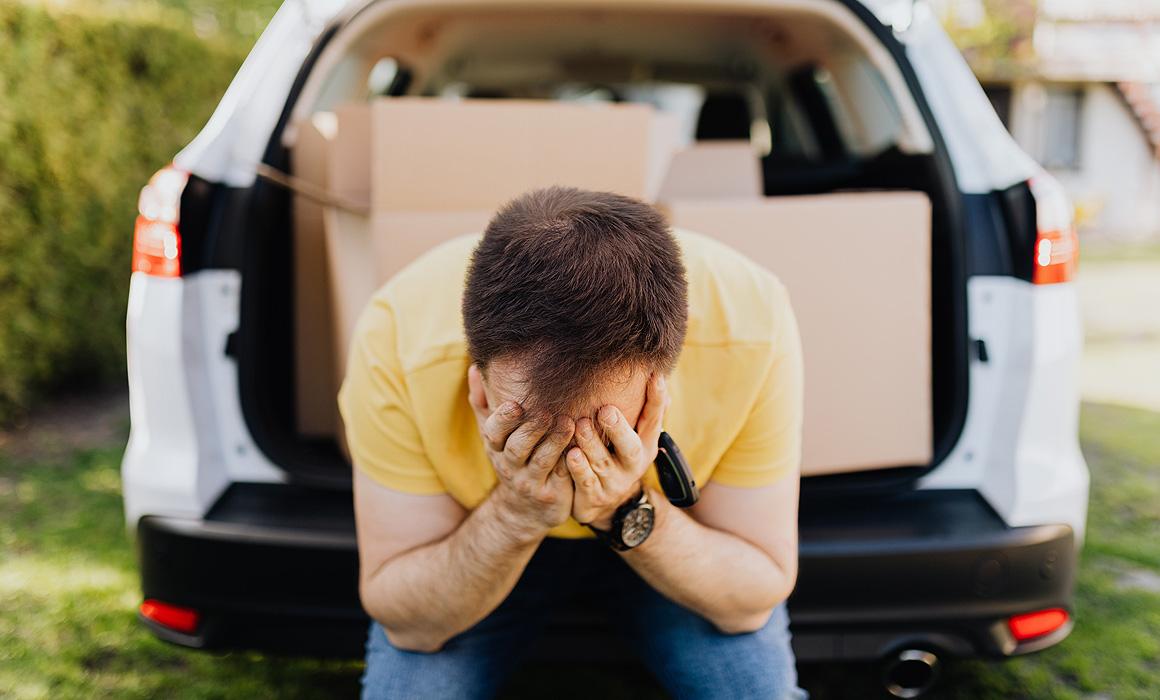 Homme accablé à l'arrière d'une voiture remplie de cartons