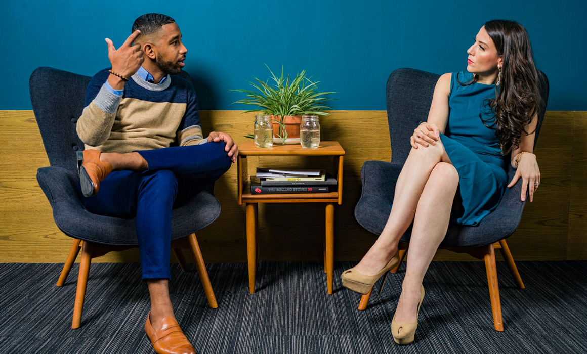 Homme et femme discutant assis sur des fauteuils