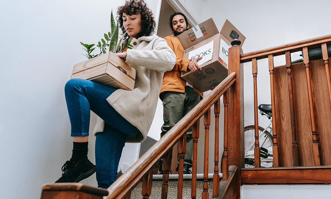 Couple portant des cartons dans un escalier