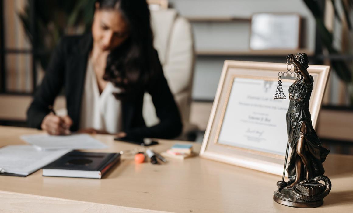 Femme assise à un bureau signant un document papier