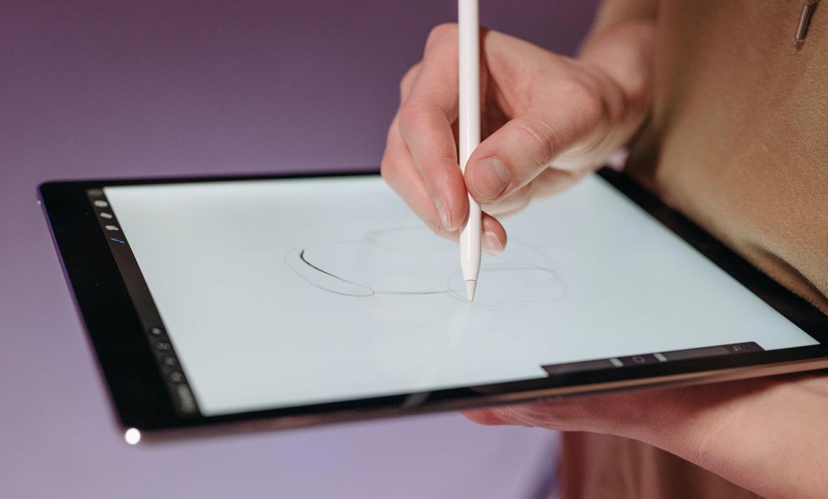 Main dessinant avec un stylet sur une tablette