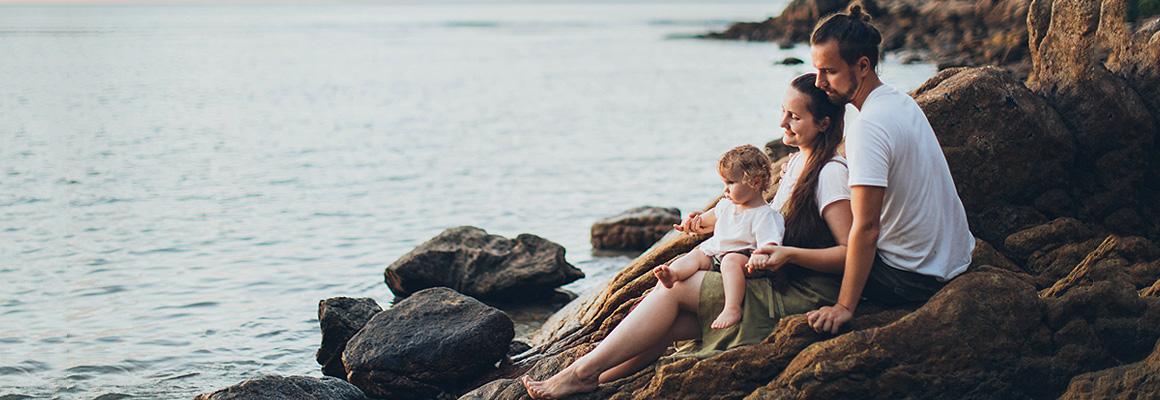 Famille assise sur des rochers en bord de mer
