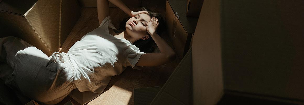 Femme allongée parmi des cartons
